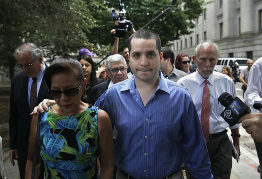 "In this Tuesday, July 1, 2014 file photo, GIlberto Valle, foreground right, leaves Manhattan federal court in New York. A federal appeals court reversed the computer-crime conviction of the ex-NYPD detective, whom tabloids dubbed the ""cannibal cop"" for his online exchanges about kidnapping and eating women, and who improperly used a police database to gather information. Valle argued that as an officer, he was authorized to access the database. The court said the statute was ambiguous and risked criminalizing a broad array of computer use. (AP Photo/Seth Wenig)"