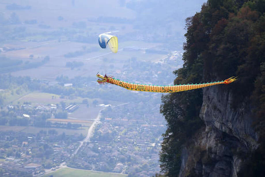 """Paraglider Gabriele D'arrigo performs a flight with a Dragon during the 43st Icare Cup paragliding festival in Saint Hilaire du Touvet, French Alps, Saturday, Sept. 24, 2016. The """"Coupe Icare"""" dedicated to free flight, orchestrates all the various types of flying such as hang gliding, paragliding and acrobatic sailplaneing. (AP Photo/Francois Mori)"""
