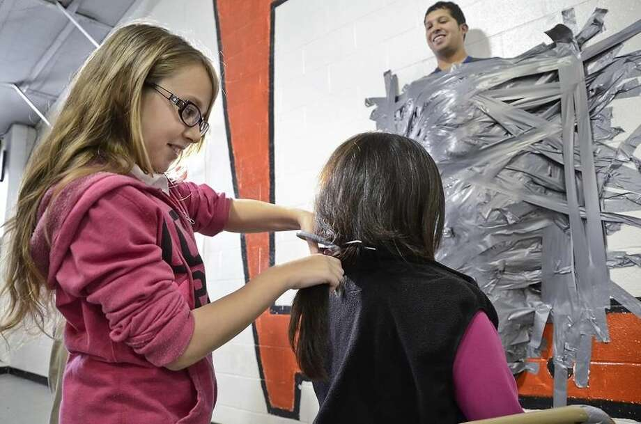 Trautmann Elementary coach Danny Gonzalez, who was taped to the wall, looks down as fellow coach Donna Garcia gets her hair cut by fifth grader Katy Cantu Wednesday morning at the school gymnasium. A group of students had the opportunity to participate in the fun event after they surpassed a challenge by both coaches to collect $3,000 at a recent Jump Rope for Heart fundraising event. The children collected $5,723.71, almost doubling the initial goal. (Photo by: Cuate Santos