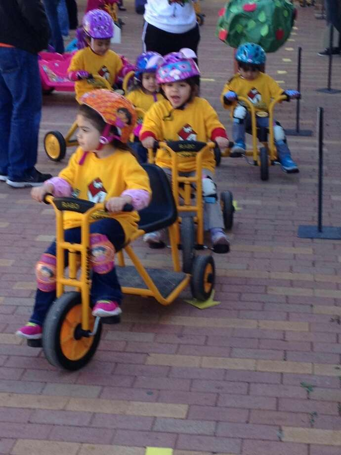Students at the Camilo Pravda Child Development Center participate in a fund-raising Trike-A-Thon at the LCC South Campus Friday morning. The event raises funds for the St. Jude Children's Research Center. (Photo by: Cuate Santos