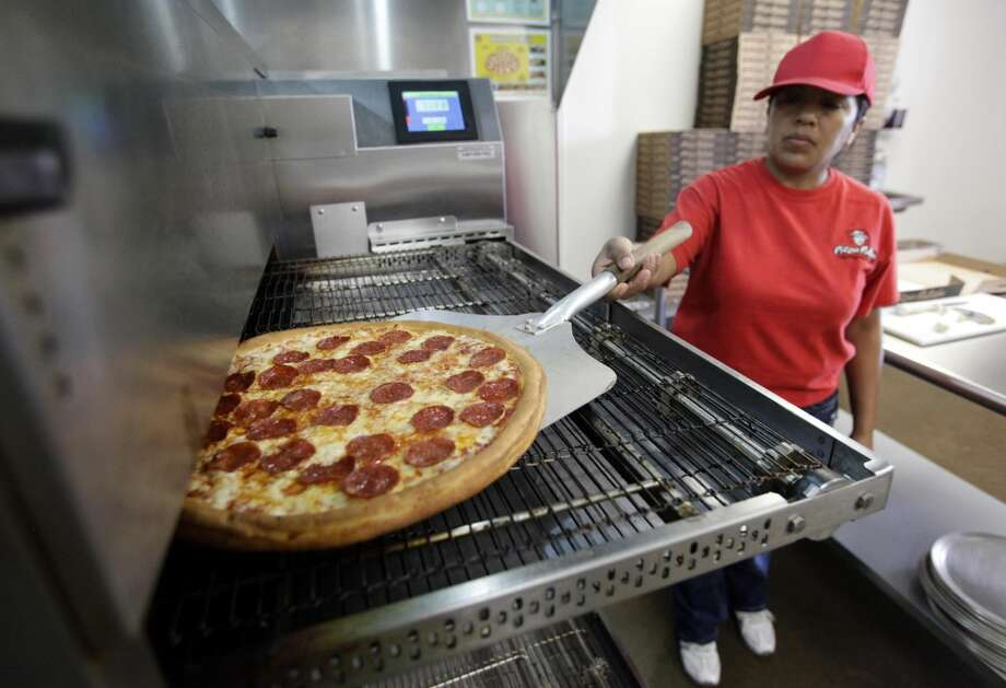 In this Thursday, May 24, 2012, photo, employee Rosy Tirado pulls a pepperoni pizza from an oven at a Pizza Patron Dallas, Texas. While lower-wage American workers have accounted for the lion's share of the jobs created since the 2007-2009 Great Recession, a survey released March 2013 shows that they are also among the most pessimistic about their future career prospects, their job security and their finances. (AP Photo/Tony Gutierrez)