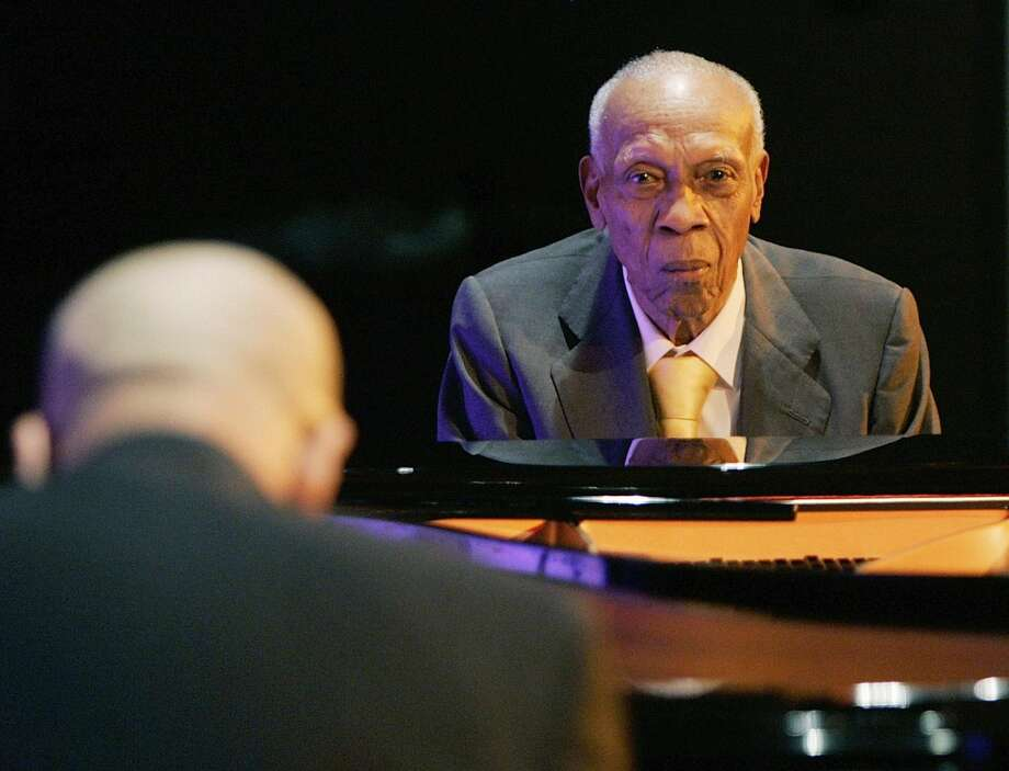 In this Oct. 9, 2008 file photo, Cuban pianist Bebo Valdes, right, and his son Chucho Valdes perform during a joint concert at the Casa de America in Madrid, Spain. Bebo Valdes died Friday, March 22, 2013 in Sweden, according to the Society of Spanish Authors without specifying the cause of death. He was 94. (AP Photo/Paul White, File)