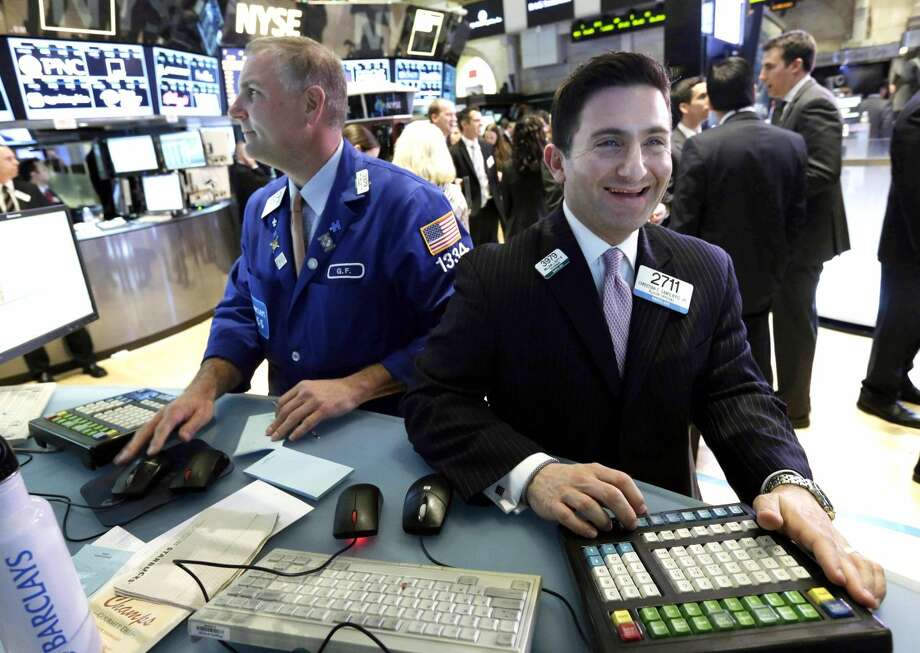In this Tuesday, March 5, 2013, file photo, specialist Christian Sanfillippo, right, smiles as he works at his post on the floor of the New York Stock Exchange. The Dow's new all-time high and better economic data from the United States propelled world stock markets higher Wednesday March 6, 2013. (AP Photo/Richard Drew, File)