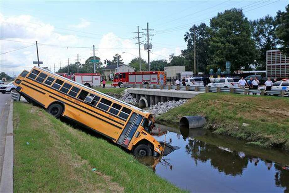 A school bus carrying 34 members of the track team from T.H. Harris Middle School crashed into the canal at Elise and West Metairie Avenues in Metairie, La. on Tuesday afternoon, Sept. 6, 2016. The Jefferson Parish Sheriff's Office said all of the students were able to get out of the bus. Three students were taken to a hospital with minor injuries. The driver was cited for careless operation. (Michael DeMocker/NOLA.com The Times-Picayune via AP)