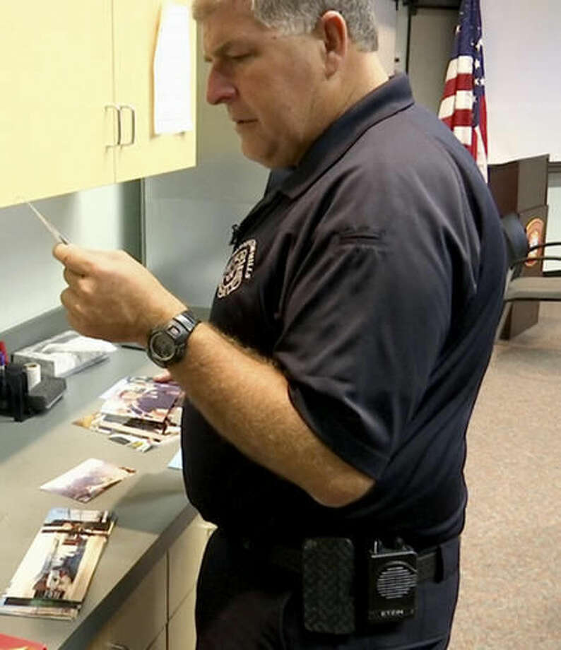 In this Aug. 22, 2016, image taken from video, EMS Coordinator Jim Etzin examines a photograph at the Farmington Hills Fire Department in Farmington Hills, Mich. The photo was taken nearly 15 years earlier when Etzin, then a Farmington Hills firefighter/paramedic, and eight other members of southeastern Michigan's firefighting community took part in a 755-mile walk from the Ambassador Bridge in Detroit to the Brooklyn Bridge a month after the Sept. 11, 2001, terror attacks. (AP Photo/Mike Householder)