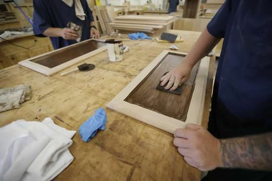 In a photo from Friday, July 8, 2016, inmates work on staining cabinet doors at the Habitat for Humanity Prison Build at the Ionia Correctional Facility in Ionia, Mich. Few states have been more aggressive in releasing inmates and diverting offenders than Michigan, where the prison system has long threatened the state???s capacity to fund universities and other basics of government. But the $2 billion annual cost remains steep, exacerbated by a boomerang found here and across the country: the large number of inmates who wind up back behind bars again. Now Michigan leaders, frustrated that their downsizing efforts have hit a wall, are trying novel, more hands-on methods to ensure that prisoners leave with a job in hand. (AP Photo/Carlos Osorio)