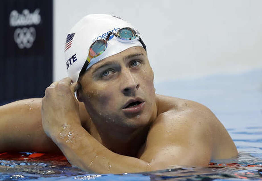 FILE - In this Tuesday, Aug. 9, 2016, file photo, United States' Ryan Lochte checks his time in a men's 4x200-meter freestyle heat at the 2016 Summer Olympics, in Rio de Janeiro, Brazil. Lochte is banned from swimming through next June and will forfeit $100,000 in bonus money that went with his gold medal at the Olympics, part of the penalty for his drunken encounter at a gas station in Brazil during last month's games. The U.S. Olympic Committee and USA Swimming announced the penalties Thursday. (AP Photo/Michael Sohn, File)