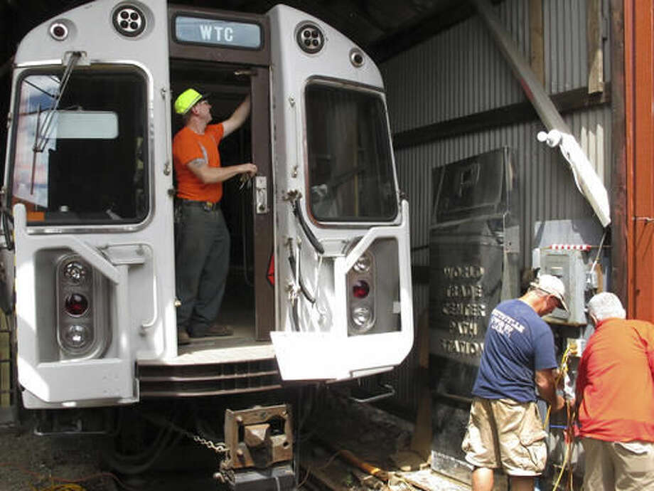 In this Aug. 17, 2016 photo, Conrad Misek, left, a conservator for the Shore Line Trolley Museum, opens a door to PATH car 745 at the museum in East Haven, Conn. The subway car was beneath the World Trade Center in New York during the terrorist attack on Sept. 11, 2001. The museum will dedicate and open to the public an exhibit featuring the car on Sept. 11, 2016. (AP Photo/Dave Collins)
