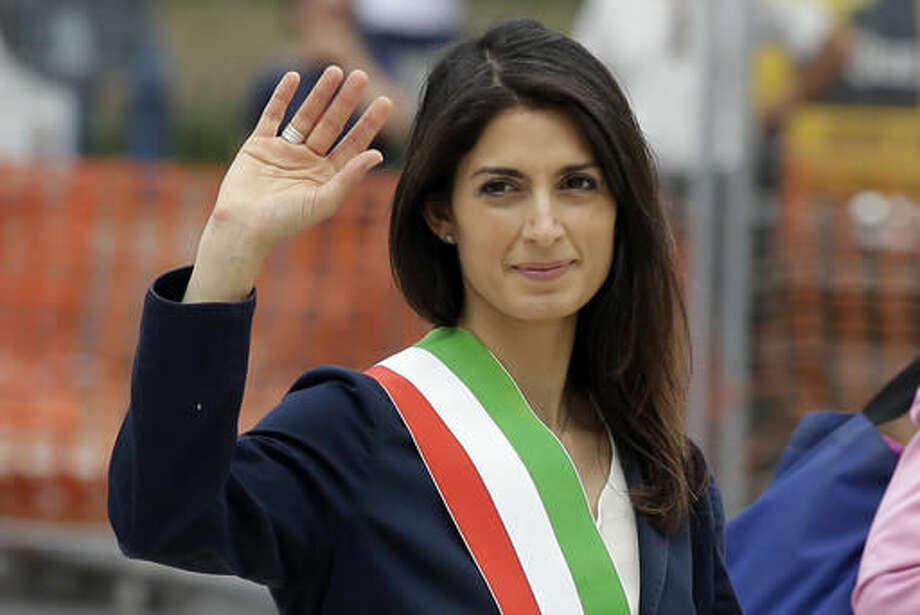 "FILE - In this Thursday, June 23, 2016 file photo, Rome's Mayor Virginia Raggi waves to reporters as she leaves the Rome's Vittoriano Unknown soldier monument, after laying a wreath. The day the anti-establishment 5-Star Movement triumphed in Rome's mayoral election, its exultant founder, comic Beppe Grillo, immediately turned his supporters' sights on the next destination for what he calls their ''mission impossible airplane"" soaring into national power. (AP Photo/Gregorio Borgia, File)"