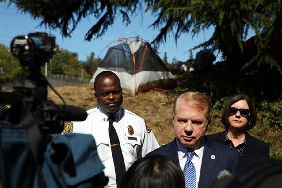 Flanked by Seattle Fire Chief Harold Scoggins, left, and Seattle Police Chief Kathleen O'Toole, right, Mayor Ed Murray speaks to the media at the site of a fatal accident that left one person dead when a car ran into a homelessness encampment near the 50th St NE Interstate 5 off-ramp in the University District, Monday, Sept. 12, 2016. (Genna Martin/seattlepi.com via AP)