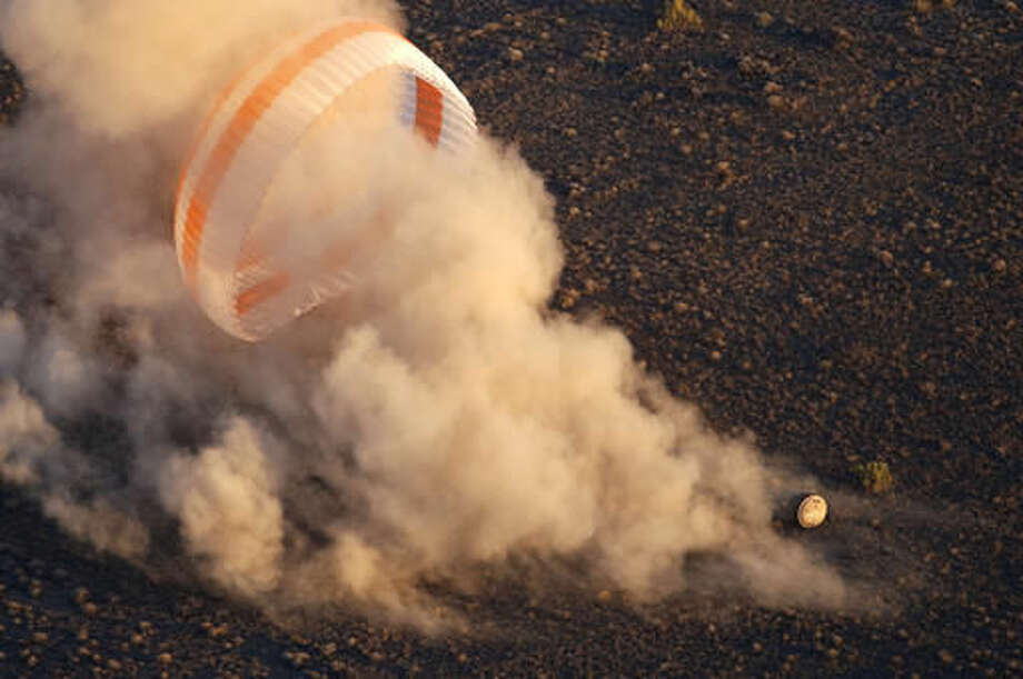 The Soyuz TMA-19M capsule carrying NASA's Jeff Williams, Russian cosmonauts Alexey Ovchinin and Oleg Skripochka touches down with its parachute near the town of Zhezkazgan, Kazakhstan, Wednesday, Sept. 7, 2016. The record-setting American and two Russians landed safely back on Earth Wednesday after a six-month mission aboard the International Space Station. (Maxim Shipenkov/Pool Photo via AP)