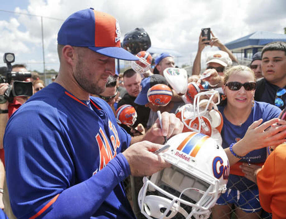 Tim Tebow signs autographs for fans at the New York Mets' complex, Monday, Sept. 19, 2016, in Port St. Lucie, Fla. The 2007 Heisman Trophy winner and former NFL quarterback got to the complex early Monday, and started his first workout as part of their instructional league team. (AP Photo/Wilfredo Lee)