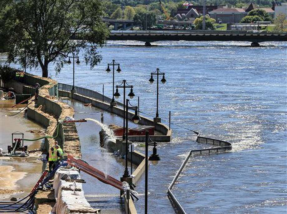 Emergency crews monitor the flood barriers along the Cedar River in Downtown Cedar Rapids, Iowa, Tuesday, Sept. 27, 2016. Officials in Cedar Rapids say their elaborate system of temporary floodwalls is successfully protecting thousands of homes and businesses from floodwaters. (Zach Boyden-Holmes/The Register via AP)