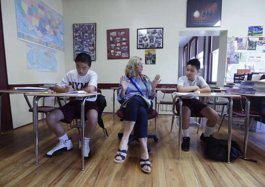 In this Thursday, Sept. 8, 2016 photo, Susan Pasquale teaches English as a second language course at the New York Military Academy in Cornwall-on-Hudson, N.Y. While Republican presidential nominee, Donald Trump, talks tough about dealing with China, his old military prep school is building bridges to that country. The New York Military Academy began classes this fall with new Chinese backing and a former New York City high school principal originally from China in charge. (AP Photo/Mike Groll)