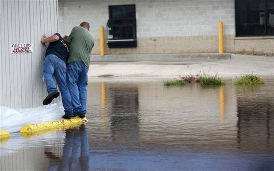 Two men check water levels near West Main Street Friday, Sept. 23, 2016 in Manchester, Iowa. Authorities in several Iowa cities were mobilizing resources Friday to handle flooding from a rain-swollen river that has forced evacuations in several communities upstream, while a Wisconsin town was recovering from storms now blamed for two deaths. (Jessica Reilly/Telegraph Herald via AP)