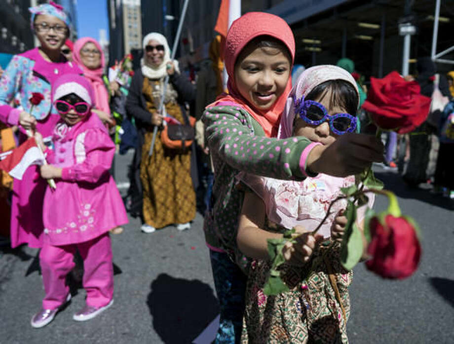 Children hand out flowers along the parade route during Muslim Day Parade on Madison Ave., Sunday, Sept. 25 2016, in New York. (AP Photo/Craig Ruttle)