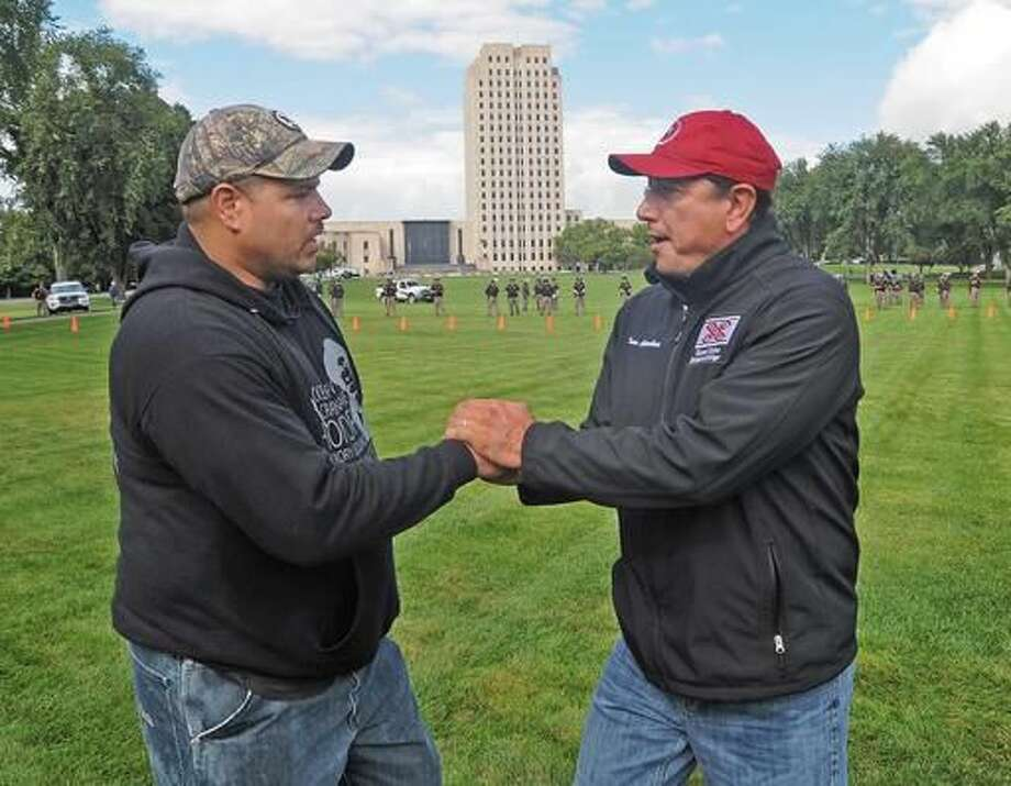 "Standing Rock Sioux tribal chairman Dave Archambault II, right, greets Wayland Gray, of Muskogee Creek Hickory Ground, Okla. at the organized protest on the North Dakota state capitol grounds on Friday, Sept. 9, 2016 in Bismarck, N.D. The federal government stepped into the fight over the Dakota Access oil pipeline Friday, ordering work to stop on one segment of the project in North Dakota and asking the Texas-based company building it to ""voluntarily pause"" action on a wider span that an American Indian tribe says holds sacred artifacts. (Tom Stromme/The Bismarck Tribune via AP)"