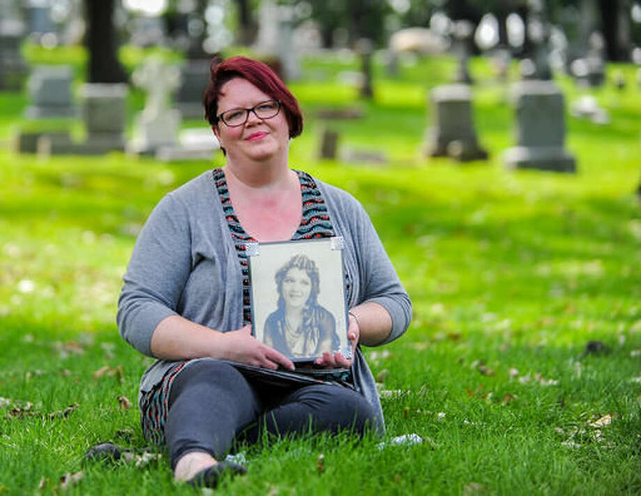 "In this Aug. 23, 2016 photo, Minda Powers-Douglas, of Moline, Ill., poses with a photograph of one of her idols, silent movie star Mary Pickford, at Oakdale Memorial Gardens in Davenport, Iowa. Powers-Douglas has a hobby to die for: cemeteries. The enthusiastic prolific writer, editor and speaker is working on a special cemetery book, ""Forever Silent: Silent Film Actresses and Their Graves."" The project's goal is to give voice to female silent-film stars. (Meg McLaughlin/The Dispatch via AP)"