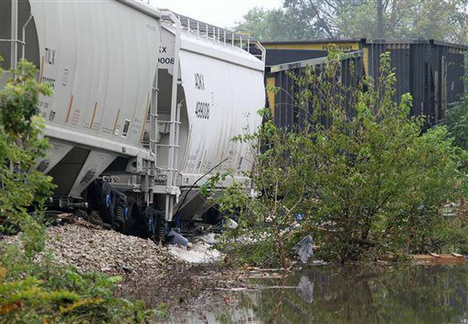 Train cars sit on track that buckled after flood waters from the Shell Rock River undermined the tracks Friday, Sept. 23, 2016, east of Main Street in Clarksville, Iowa. Authorities in several Iowa cities were mobilizing resources Friday to handle flooding from a rain-swollen river that has forced evacuations in several communities upstream, while a Wisconsin town was recovering from storms now blamed for two deaths. (John Molseed/The Courier via AP)