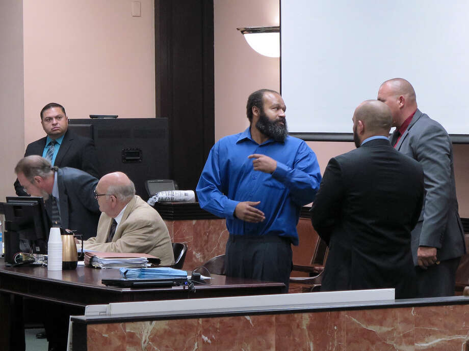 Demond Bluntson, in blue shirt, speaks to court security officers after entering the 49th District Courtroom on Monday for opening statements of his capital murder trial.
