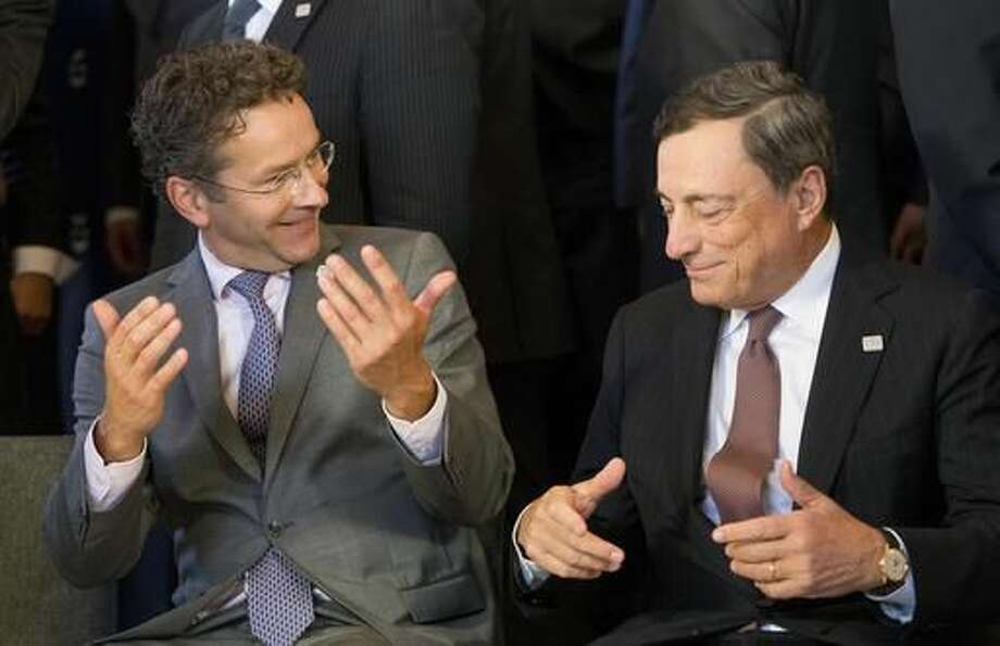 Netherlands' Minister of Finance Jeroen Dijsselbloem gestures, next to President of the European Central Bank, Mario Draghi, right, during the group photo, after the Eurogroup's deliberations at the Informal Meeting of Ministers for economic and financial affairs, in Bratislava, Slovakia, Friday, Sept. 9, 2016. Ministers for economic and financial affairs gathered for a two-day informal meeting in the Slovak capital, where they will discuss BREXIT, EU economic policies and the migration crisis. (AP Photo/Bundas Engler)