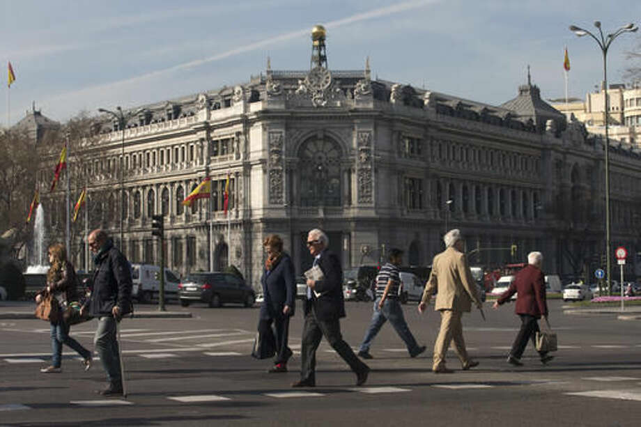 FILE - In this March 12, 2015 file photo, people cross the street in front of Spain's Central Bank in Madrid. Spain's central bank warned on Thursday, Sept. 29, 2016, that the political impasse in the country could have negative economic effects. (AP Photo/Paul White, File)
