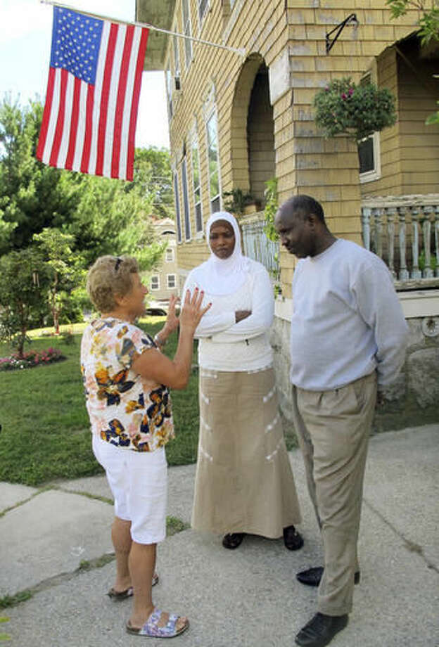 In this Sept. 16, 2016 photo, Fresh Start translator Samira Clough, left, speaks to Amna Salim Ali, center, and her husband Ezairig El Nemair in front of their home in New London, Conn. The Sudanese couple are among about 500 refugees being resettled this year by Integrated Refugee & Immigrant Services with the help of community organizations across the state. (AP Photo/Pat Eaton-Robb)