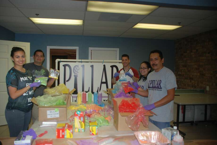 TAMIU volunteers prepare powder paint bags. From left: Liabette Rodriguez, Georgie Mariscal, Jesse Serna, Kimberly Rodriguez, and Arturo Diaz, PILLAR Co-Founder.