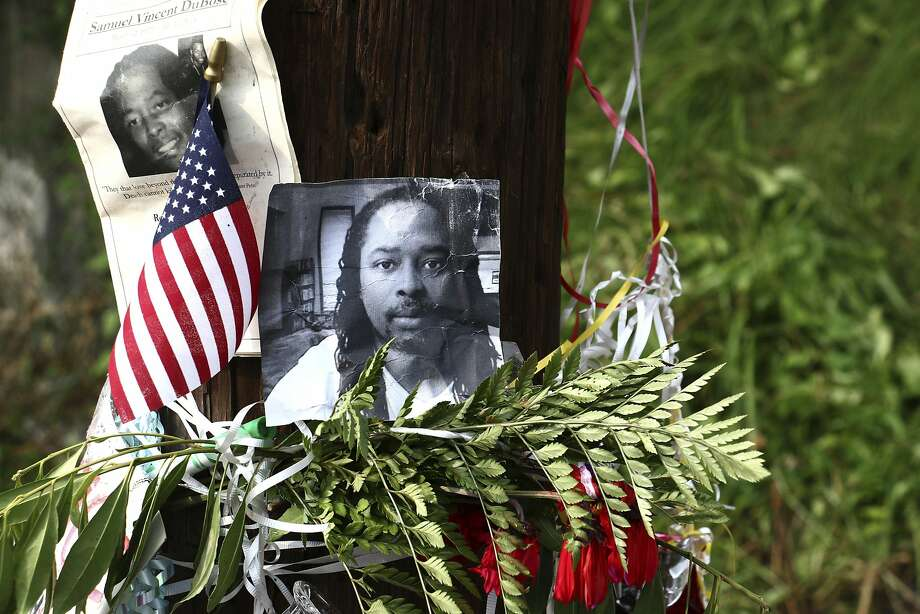 FILE — In this July 29, 2015, file photo, photos of Sam DuBose hang on a pole at a memorial near where he was shot and killed by a University of Cincinnati police officer during a July 19, 2015, traffic stop in Cincinnati. F Photo: Tom Uhlman, Associated Press