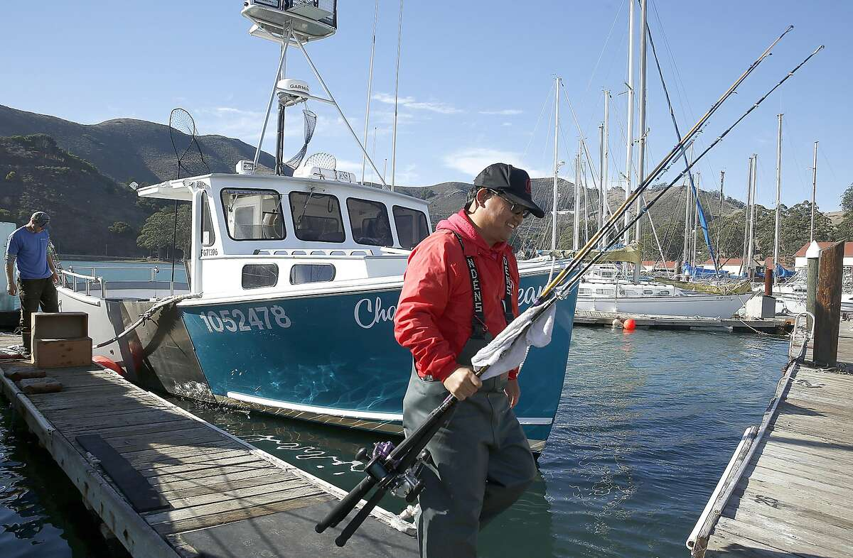 Byron Lim helps bring off fishing rods as Chasin'Crustacian returns to Fort Baker from a salmon fishing run on Friday, October 21, 2016, in Sausalito, Calif.