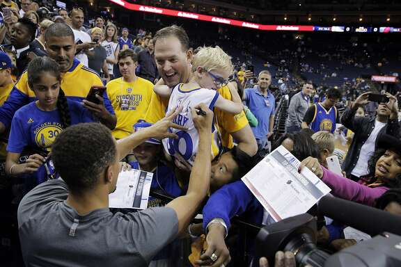 Greg Bell of Danville, holds his son Charlie, 5, up for Stephen Curry (30) to sign his jersey during warmups before the Warriors played the Portland Trail Blazers during a pre-season game at Oracle Arena in Oakland, Calif., on Friday, October 21, 2016. The Warriors won 107-96.