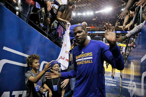 Kevin Durant (35) high fives fans after the Warriors played the Portland Trail Blazers during a pre-season game at Oracle Arena in Oakland, Calif., on Friday, October 21, 2016. The Warriors won 107-96.