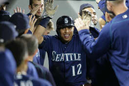 Seattle Mariners' Leonys Martin is greeted in the dugout after scoring during the eighth inning of a baseball game against the Oakland Athletics on Thursday, Sept. 29, 2016, in Seattle. (AP Photo/Ted S. Warren)