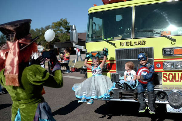 """From left, Anna, Colette and Gabriel Cannon pose for a photo with a fire truck during the Midland Fire Department's third annual """"Truck or Treat"""" open house and Halloween carnival on Saturday, Oct. 22, 2016, at the Central Fire Station. James Durbin/Reporter-Telegram"""