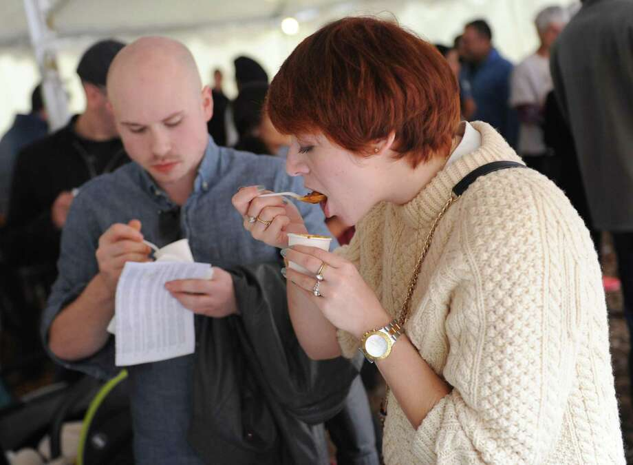 Eric Day, of Clinton, and Julianne Giordano, of Stamford, sample cups of chili at the Eighth Annual Stamford Charity Chili Cookoff at the Stamford Museum and Nature Center in Stamford, Conn. Sunday, Nov. 1, 2015.  More than 15 vendors gave out samples of chili to benefit the Food Bank of Lower Fairfield County. This event was also part of the Nature Center's Touch-a-Truck event where kids got the chance to sit in and play around large farming, construction and city trucks. Photo: Tyler Sizemore / Hearst Connecticut Media / Greenwich Time