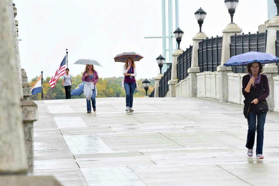 Pedestrians cross the bridge from Riverfront Park on a rainy day on Friday, Oct. 21, 2016 in Albany, N.Y. Photo: Lori Van Buren