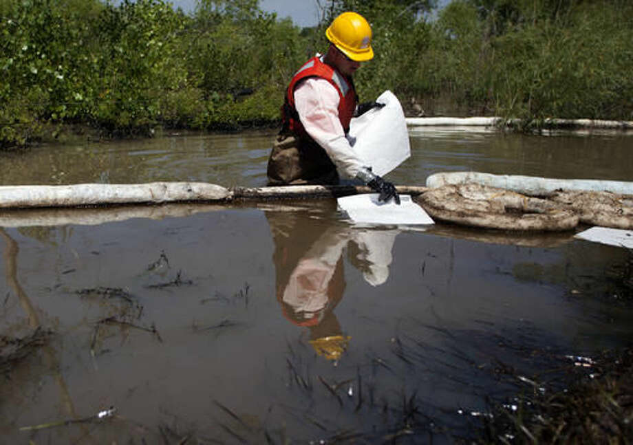 FILE - In this July 6, 2011, file photo, cleanup workers use oil absorbent materials along side the Yellowstone River in Laurel, Mont., to clean up an oil spill. Exxon Mobil Corporation has agreed to pay about $12 million for damages caused by the 2011 pipeline break that spilled gallons of crude into Montana's Yellowstone River, officials said Wednesday, Sept. 21, 2016. (AP Photo/Jim Urquhart, File)