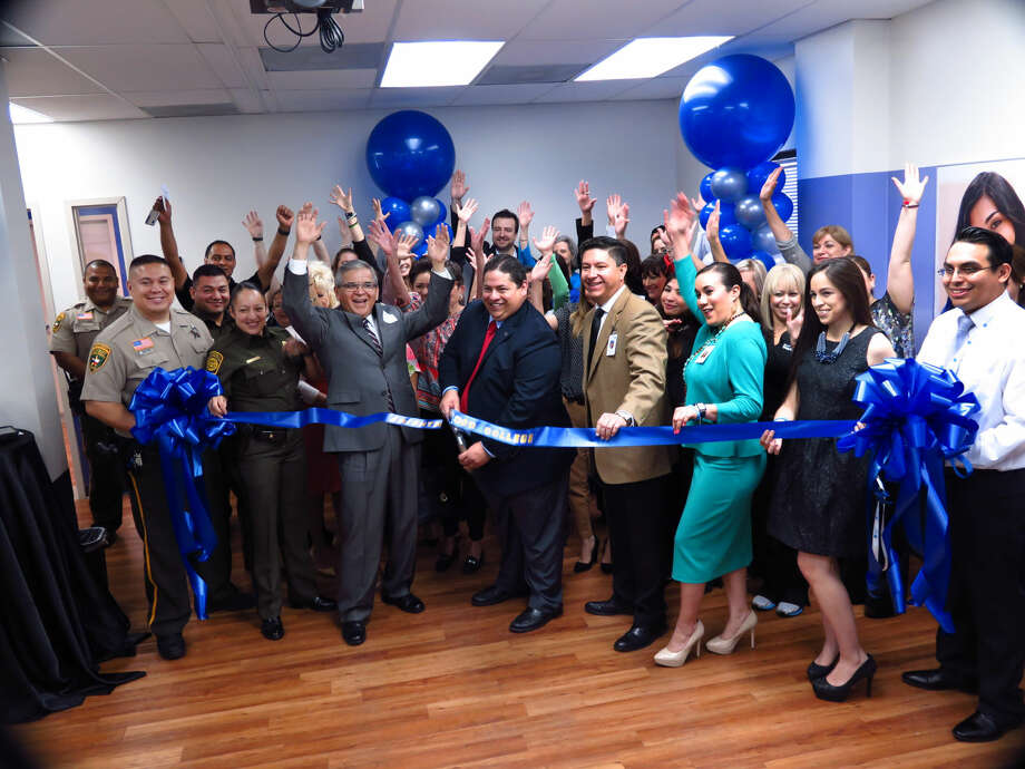 Brightwood College Laredo Campus President Jorge Hinojosa cuts the ribbon as college directors, Laredo Chamber of Commerce representatives and members of the community cheer him on Wednesday morning.