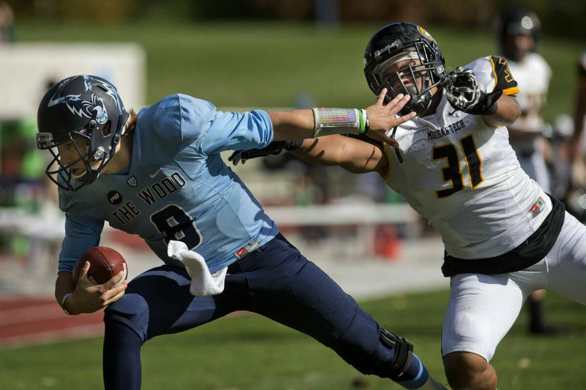 Northwood University's quarterback Joe Garbarino works to evade a tackle from Michigan Tech's Marvin Wright in the first half of the Saturday afternoon game.