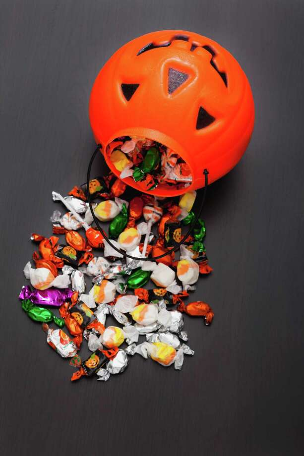Candies spilling from Jack O'Lantern basket, studio shot Photo: Vstock LLC / Tetra images RF