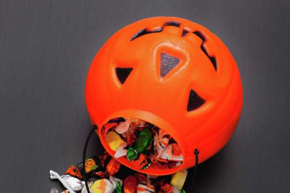 Candies spilling from Jack O'Lantern basket, studio shot