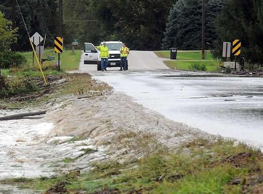 City of Mankato workers watch water flow over Indian Lake Road near Mount Kato Ski Area Thursday, Sept. 22, 2016 in Mankato, Minn. Overnight heavy rains caused flooding and mudslides. (Pat Christman/The Free Press via AP)