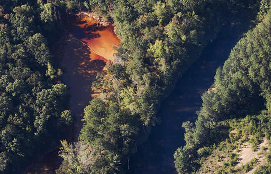This aerial photo shows a pair of water retention ponds at the site of a pipeline leak, Tuesday, Sept. 20, 2016, near Helena, Ala. The retention pond on the left is where the gasoline has been contained. A main gas line is expected to restart Wednesday with a temporary bypass after a leak and spill in Alabama led to surging fuel prices and some gas shortages across the South, a Colonial Pipeline official said Tuesday. (AP Photo/Brynn Anderson)