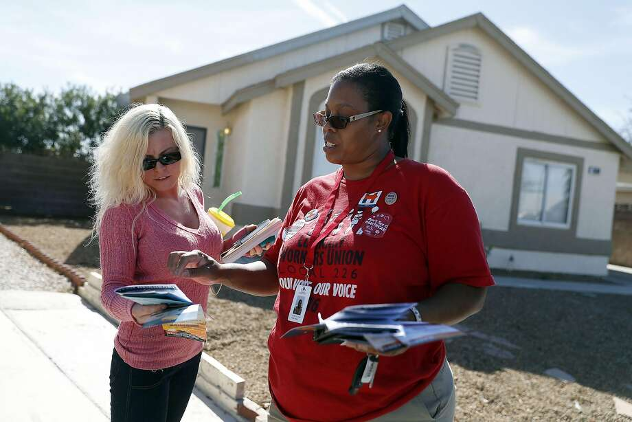 Top: Culinary union member Annette De Campos (right) talks with voter Amber Starke as she canvasses a neighborhood in Las Vegas. Above: Images of Donald Trump sit on the shelves at the union hall. Photo: Isaac Brekken, Special To The Chronicle