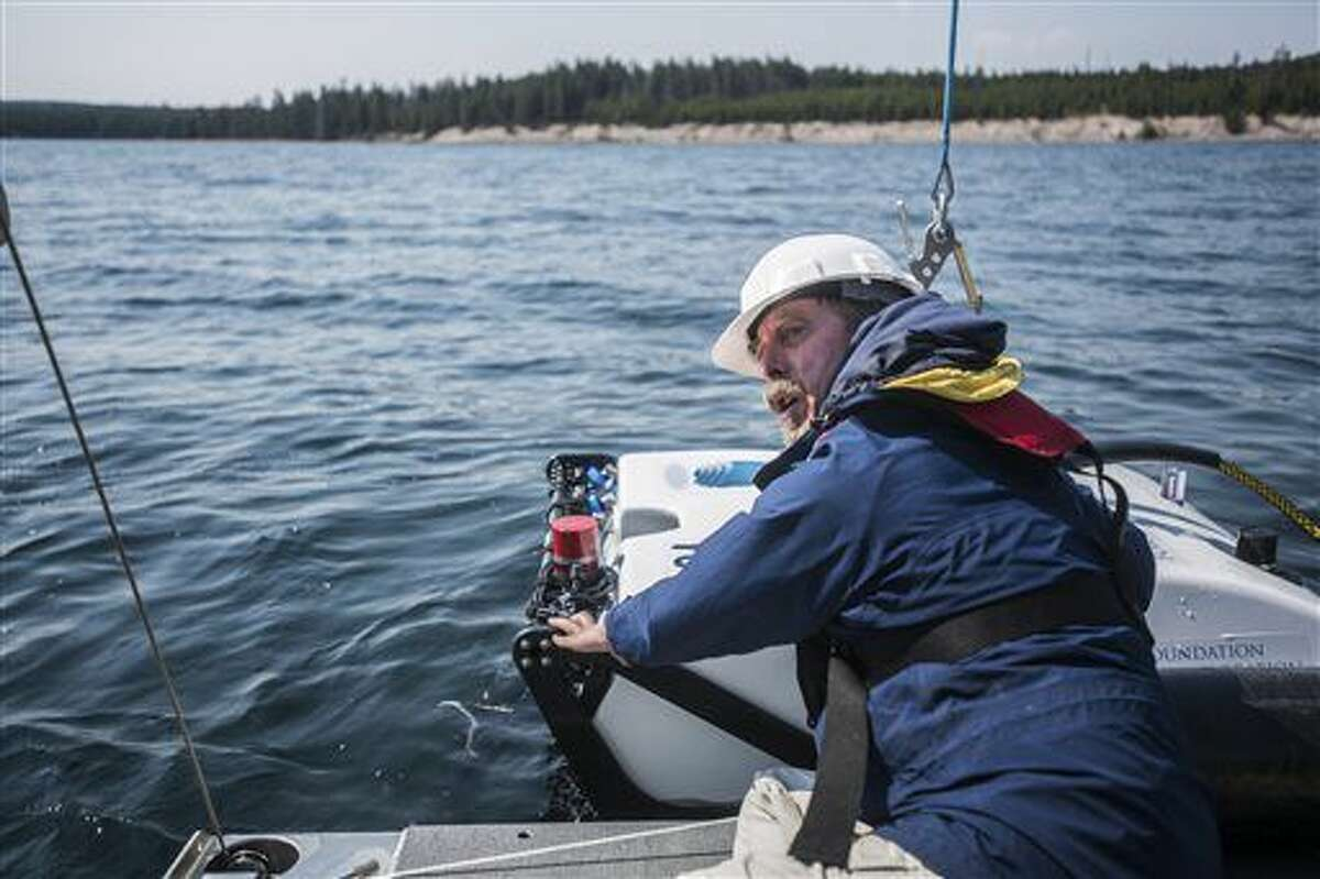 In this Aug. 24, 2016 photo, after a successful retrieval of decades-old temperature gauges from the lake bottom, senior electronics engineer of Global Foundation for Ocean Exploration Dave Wright prepares Yogi for another dive on Yellowstone Lake, in Yellowstone National Park, in Wyo. The remote-operated vehicle is submersible to depths up to 1,500 meters - nearly 5,000 feet - which means the foundation could use it to explore any lake in the United States. (Ryan Dorgan/Jackson Hole News & Guide via AP)