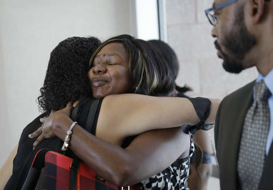 """Clark County public defender Belinda Harris, center, embraces Erika Ballou, a deputy Clark County public defender, outside of court, Thursday, Sept. 22, 2016, in Las Vegas. Ballou had agreed to remove a """"Black Lives Matter"""" pin after Clark County District Court Judge Douglas Herndon held firm and said he wouldn't allow displays of political viewpoints during proceedings in his courtroom. Ballou was in court to represent a client at a sentencing hearing in a domestic violence case. (AP Photo/John Locher)"""