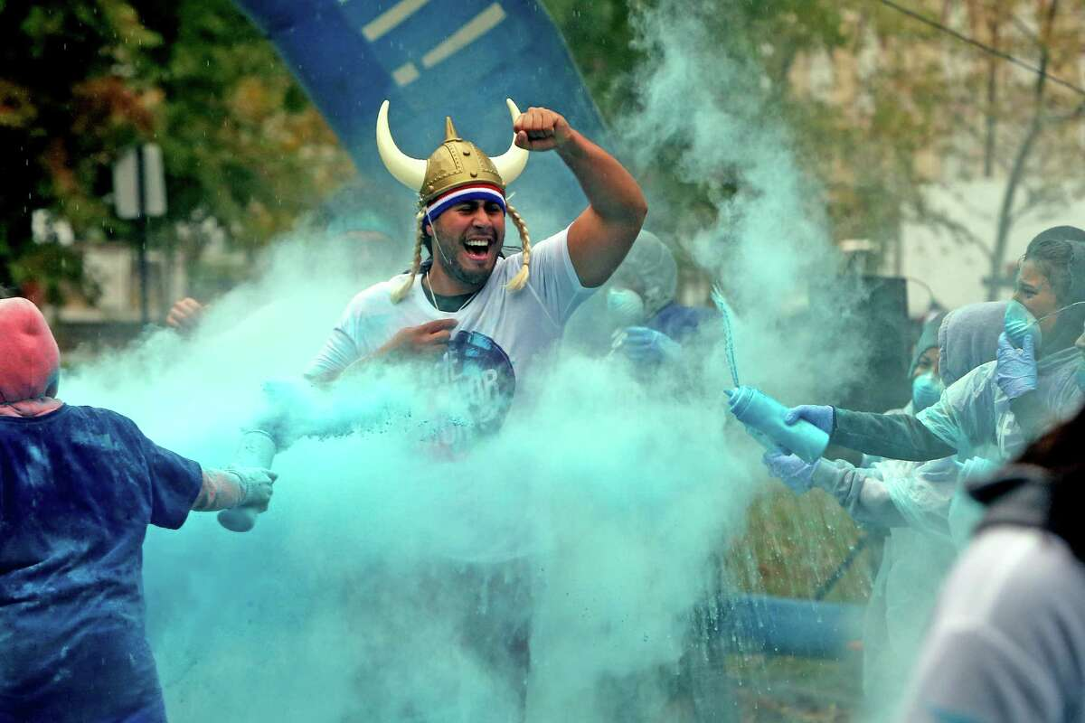 Ken Claudio, an Ansonia resident, runs through a cloud of blue powder during the 5K Color Run through Seaside Park in Bridgeport, Conn. on Saturday morning, Oct. 22, 2016.