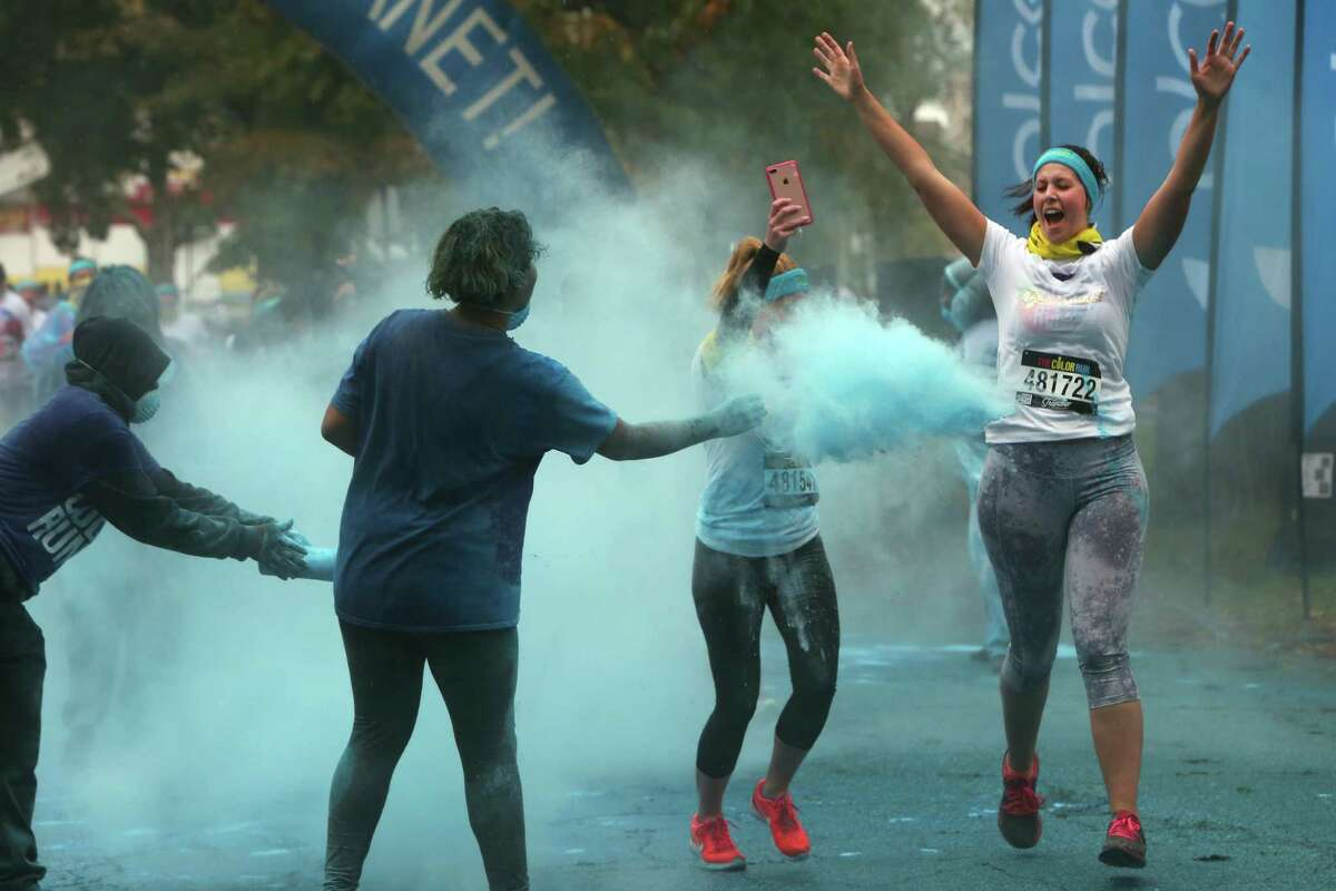 Ashley Leach, a Shelton resident, raises her arms while friend, Jessica Heisler records their experience as they're both doused in blue powder during the 5K Color Run through Seaside Park in Bridgeport, Conn. on Saturday, Oct. 22, 2016.