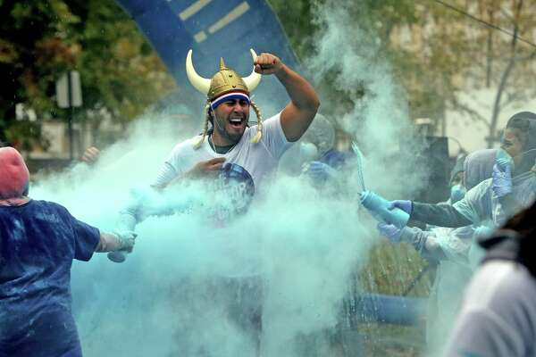 Ken Claudio, an Ansonia resident, runs throug a cloud of blue powder during the 5K Color Run through Seaside Park in Bridgeport, Conn. on Saturday morning, Oct. 22, 2016.