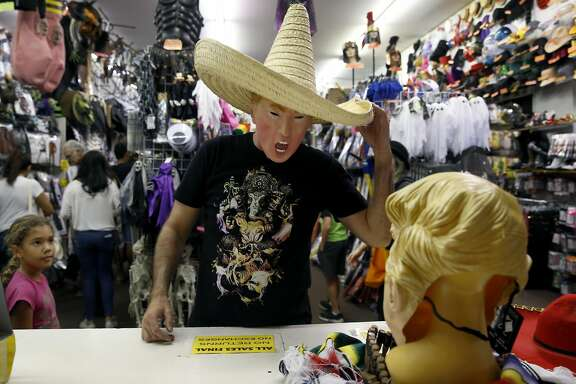 """Jay Franco tries on a Donald Trump """"Bad Hombre"""" Halloween costume at House of Humor in Redwood City, Calif. on Saturday, Oct. 22, 2016."""